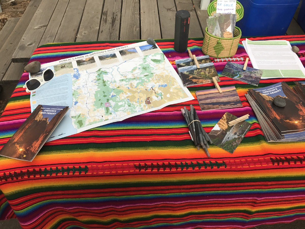 Picture of maps, brochures, and photos spread out on a tablecloth on a picnic table