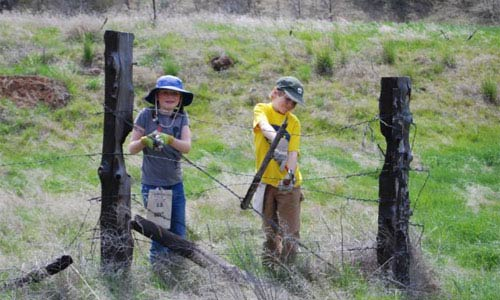 Young ONDA volunteers helping to remove obsolete barbed wire fence.